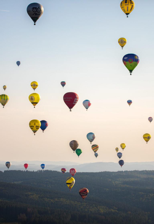 Duzende Heißluftballons bei der Warsteiner Montgolfiade über der Wald-Landschaft rund um Warstein