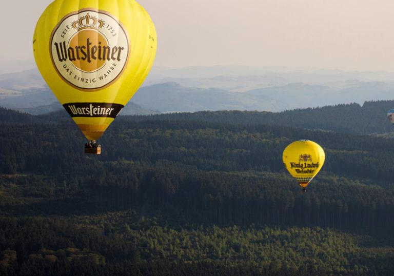 Zwei gelbe Heißluftballons mit Warsteiner und König Ludwig Weissbier Aufschrift über Wald-Landschaft in Abendstimmung